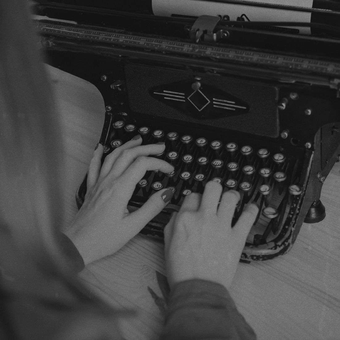 A woman typing a letter on a typewriter.