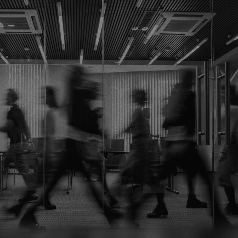 Silhouettes of people rushing through an office building.