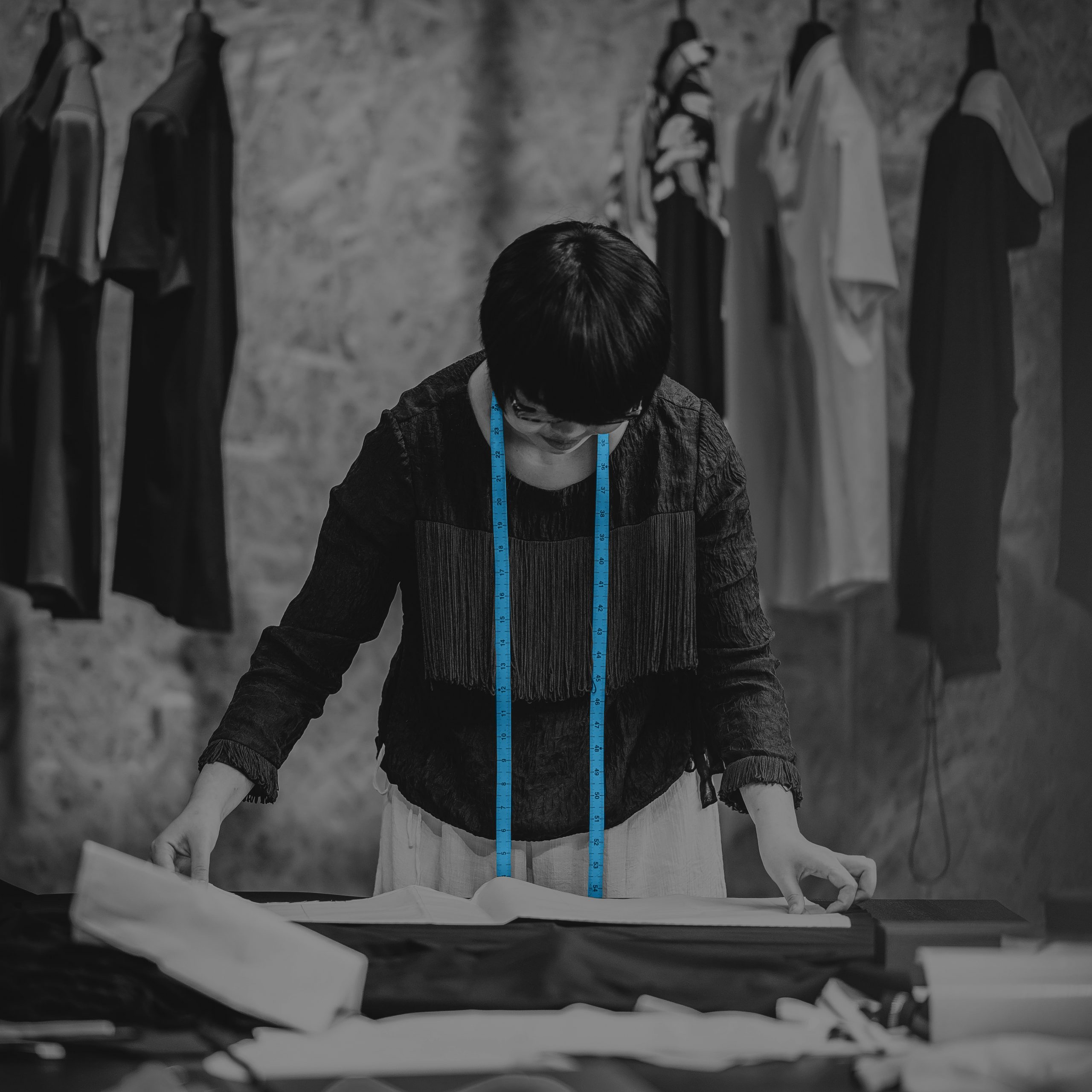 Seamstress at work with measure tape around her neck